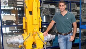 Daniel Falcón, ayer junto a un robot y ordenadores de vieja generación en la Escuela de Informática de la ULPGC. | santi blanco
